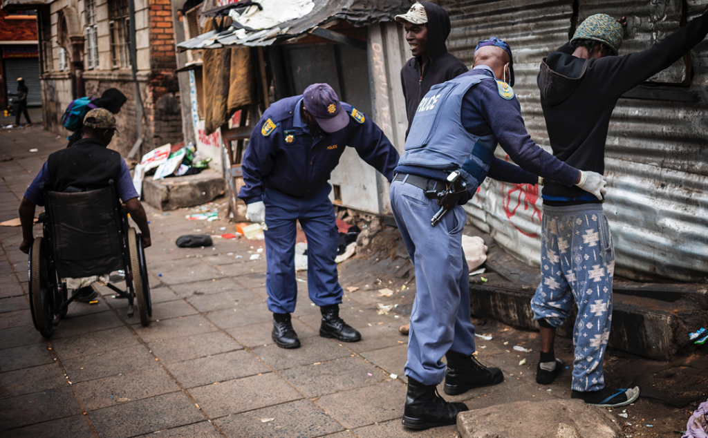 Police in Gauteng search street people in a area used by the homeless during the national lockdown